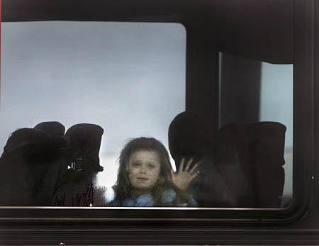 A young FLDS girl waves as she is taken away from the San Angelo Coliseum in one of the final buses to leave the arena in late April.