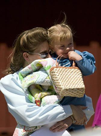 A woman from the Fundamentalist Church of Jesus Christ of Latter Day Saints leaves the Kidz Harbor facility in Liverpool, Texas with her child.