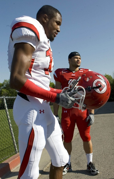 Ute football players Robert Johnson, left, and Darrell Mack model the team's new uniforms made by Under Armour.