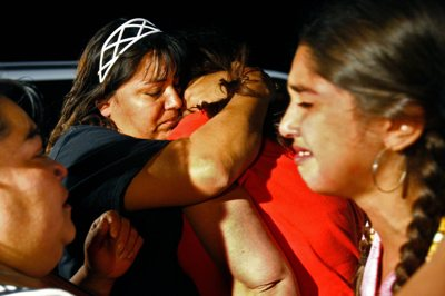 Norma Florez, back left, embraces Maria Lerma, back right, as Alejandra Valdez, front left, and Adilene Lerma, front right, embrace by the entrance to the mine in Crandall Canyon Thursday evening. Maria's husband Natalio Lerma was uninjured in the latest bump.
