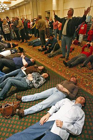 Like rows of dominoes, people fall to the Ogden floor after the Rev. Rodney Howard-Browne lays his hands on them at Tuesday's revival.