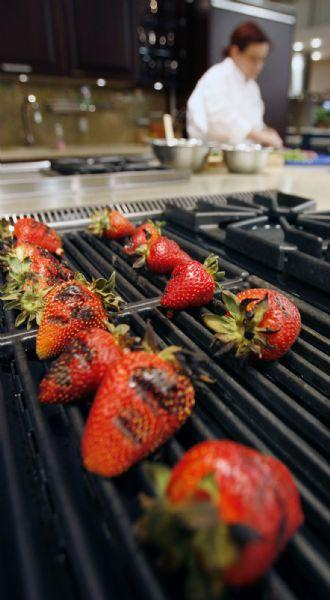 Chef Cathie Mooere grills strawberries as she mixes seasonings together at the Viking Cooking School in Salt Lake City.