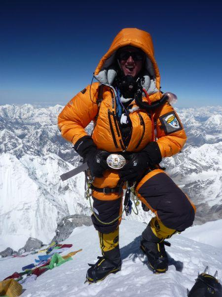 Johnny Collinson on the top of Everest in May 2009 with a belt buckle he won in ski race.