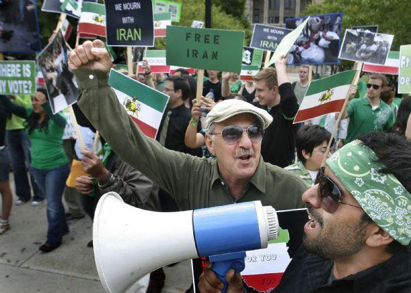 Javad Bagbani, center, chants slogans as he and other protesters, led by Sarab Mirmontazeri (on megaphone), at a rally in support of protesters in Iran. It culminated in a march to the State Capitol and a brief appearance by Utah Attorney General Mark Shurtleff.