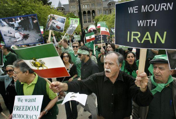 Bahram Khial, third from right, chants with people in support of protesters in Iran at the City and County Building on Saturday.