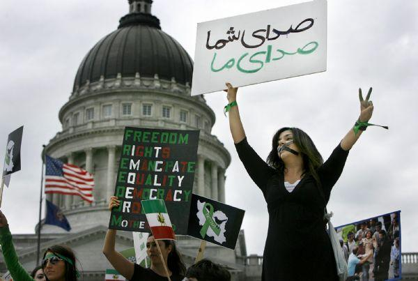 Maryam Husseini holds a sign that translates from Farsi as