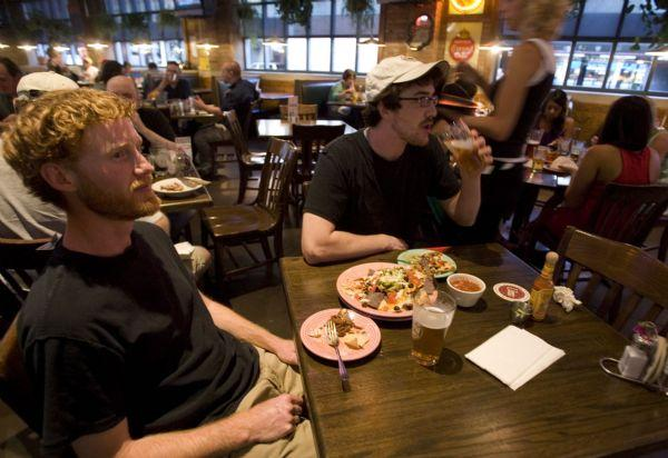 Nick Jennings, left, and Joe Aragon, both of Salt Lake City, enjoy a meal and drinks while watching sports at the Fiddler's Elbow Saturday, June 27, 2009 in Salt Lake City. A new law takes effect that will no longer the establishment to be a private club. Jim Urquhart/The Salt Lake Tribune; 6/27/09