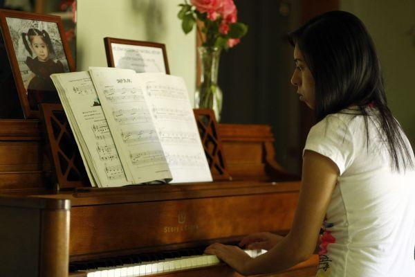 Jimena Arellano, 17, practices the piano at her home in Salt Lake City May 28, 2009. Arellano received the piano two years ago through the Mundi Piano Project.    Chris Detrick/The Salt Lake Tribune