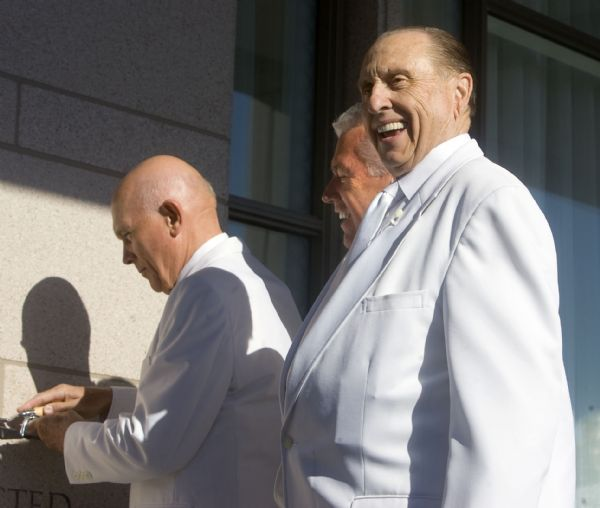 LDS Church President Thomas Monson, right, flashes a smile to those gathered for the cornerstone setting ceremony for the Oquirrh Mountain Utah Temple in South Jordan. Applying mortar, at right, is Dallin Oaks, one of the church apostles. Behind Monson is second counselor Deiter Uchtdorf.