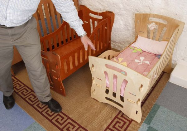 Carvel Nielsen points out the functionality of the custom-designed furniture at the Eddie Craft store in Colorado City. This crib converts into a rocker, and the side panels are adjustable.