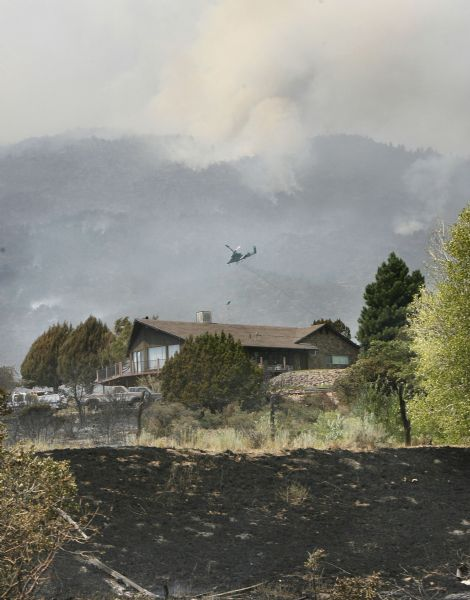 A home was saved by firefighters from the fire that raged through New Harmony on Saturday night. Helicopters continued to make preventive drops Sunday. The fire could be seen on the hillside above town in the upper background.