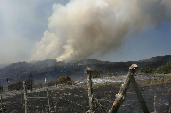 A charred field in New Harmony is seen Sunday. The fire rages on the hillsides west of town.