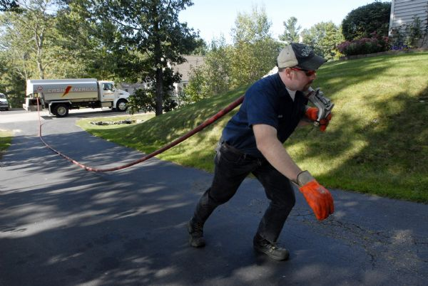 Kieth Franklin a delivery driver for Cash Energy drags the oil hose up a driveway in Old Orchard Beach, Maine for a delivery on Friday, Sept. 25, 2009.