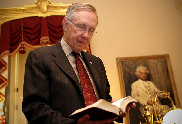 Senate Majority Leader Harry Reid, D-Nev., takes time in his Capitol office to show the Book of Mormon he keeps in his desk. He keeps an extra to give away. Reid says he is used to brickbats from fellow members who say his politics put him at odds with his faith.