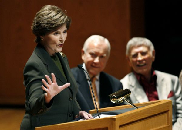 Former First Lady Laura Bush speaks at the annual Utah Women?s Conference at Abravanel Hall in Salt Lake City. Senator Orrin Hatch (R-Utah) listens in the center background, and pianist Roger Williams is at right.