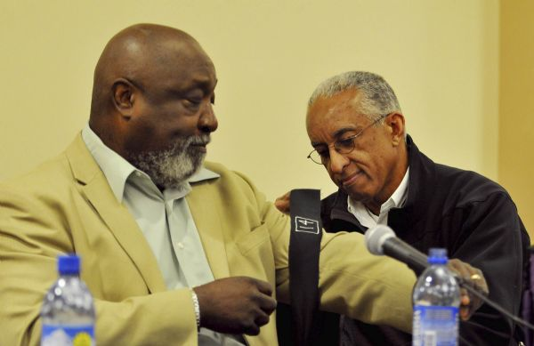 John Griffen, right, ties a black armband on the arm of his former teammate Mel Hamilton prior to The Black 14 panel discussion in the Central Ballroom Tuesday November 3, 2009 in Laramie, Wyo. The discussion marks the 40-year anniversary when in 1969 14 Wyoming football players were kicked off the team as they planned on wearing black armbands during a game against BYU. (Photo by Andy Carpenean/Laramie Boomerang)
