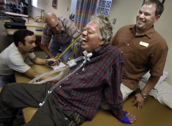 Dominic Echeverria, far right, an occupational therapist at South Davis Rehabilitation Center, can always get a laugh out of Hopkins, even during tough exercises to increase his upper body strength performed while others measure him for the carry chair. Echeverria crafted a homemade hand support for Hopkins so he could use a joystick rather than a head-activated mechanism to drive his wheelchair.