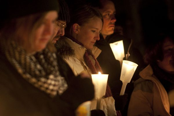 Jessica and Paul Timpson, center, gather Thursday for a candlelight vigil for Susan Powell at West View Park.