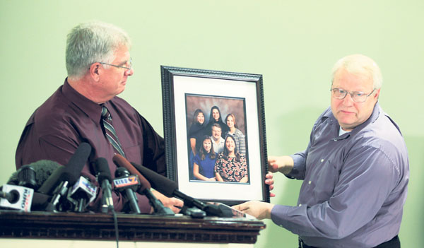 Chuck Cox, right, the father of Susan Powell, who was reported missing Dec. 7, is helped Thurs�day by family friend Michael Gifford, left, as he talks to reporters in Puyallup, Wash., about a photo of his family, which includes Susan at the upper right.