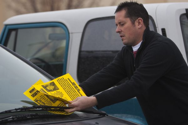 Paul Timpson puts missing-person fliers on cars in a Smith's parking lot Saturday.