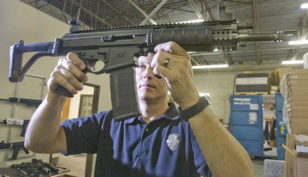 Alex Robinson, owner and manager of Robinson Armament Co.,  holds up the company's XCR rifle. The company, which employs 15 people in Salt Lake City, would be one of several firearms manufacturers marginally affected by a proposed gun-rights law. The legislation would exempt guns made, sold and kept in-state from federal weapons laws.