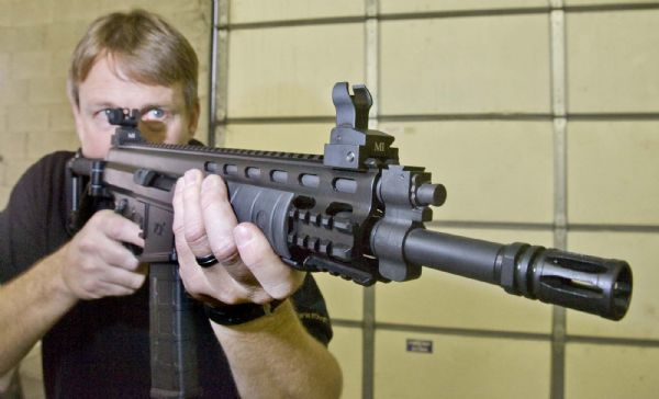 Alex Robinson, owner and manager of Robinson Armament Co.,  puts the company's XCR rifle up to his shoulder. The company, which employs 15 people in Salt Lake City, would be one of several firearms manufacturers marginally affected by a proposed gun-rights law. The legislation would exempt guns made, sold and kept in-state from federal weapons laws.
