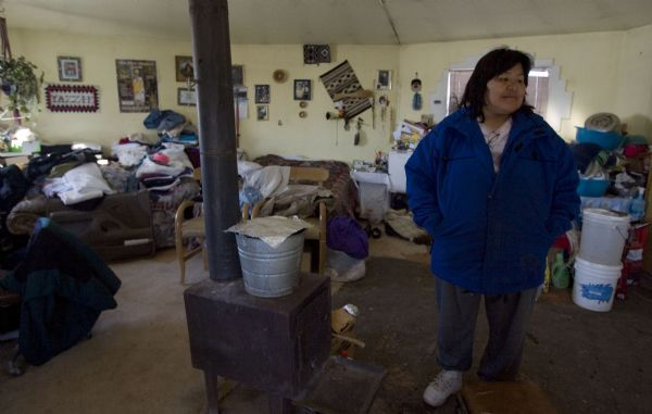 Winifred Begaye near a wood burning stove, her source of heat, in her one room home that does not have electricity or running water Monday, January 4, 2010, in the Whiterocks Point area outside Bluff, Utah. Begaye never had running water or electricity while growing up. She hauls her water from a church about five miles away and cuts firewood from the shores of the nearby San Juan River. The State of Utah is expected to announce a settlement over a decades old lawsuit involving the Utah Navajo Trust.