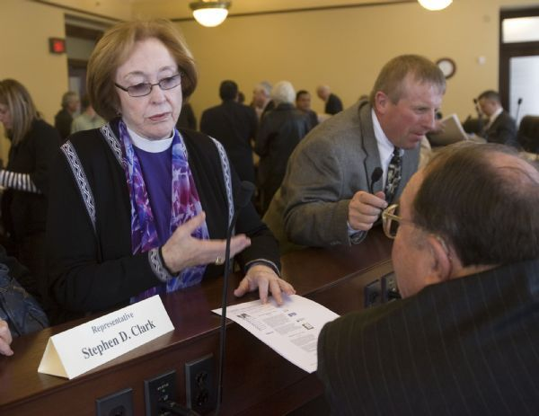 State Rep. Stephen Clark, bottom right, listens to Episcopal Bishop Carolyn Tanner Irish, left, after a meeting of the immigration committee in December 2008.