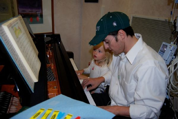 Before his heart transplant, Paul Cardall plays the piano with his daughter Eden.