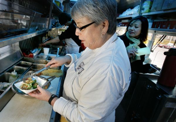 In the cramped space inside The Chow Truck, chef Rosanne Ruiz, left, makes an order under the blue light of the tinted roof while co-owner SuAn Chow handles orders. The Chow Truck is a bright yellow food truck that serves gourmet tacos and sliders.