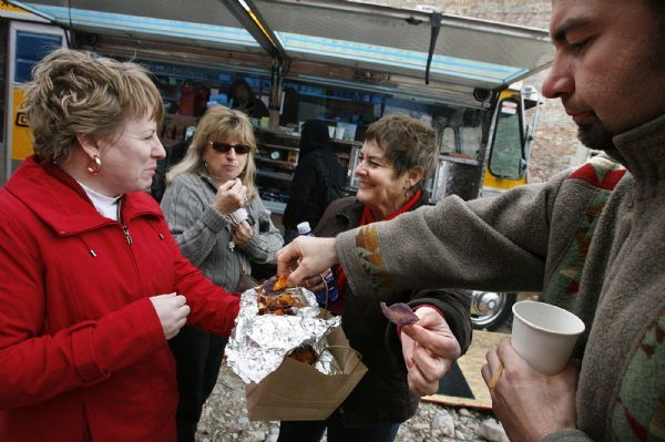 THE CHOWTRUCK  Customers (left to right) Jennifer Baumgartner, Pat Aoyagi, Mitzi MacKay, and Sweeney Windchief (all cq) sample some home-made chips from the Chow Truck after they picked up their completed order. The Chow Truck is a bright yellow food truck that serves gourmet tacos and sliders. The owners are SuAn Chow (the original owner of Charlie Chow's) and chef Rosanne Ruiz (Capital Cafe, Sage's Cafe and Vinto)