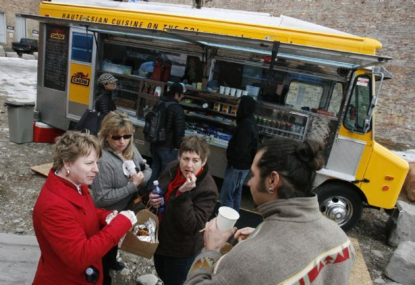 From left, Jennifer Baumgartner, Pat Aoyagi, Mitzi MacKay, and Sweeney Windchief sample some home-made chips from the Chow Truck after they picked up their completed order.  The Chow Truck is a bright yellow food truck that serves gourmet tacos and sliders.
