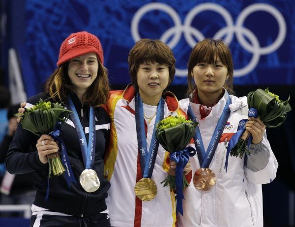 Gold medallist Wang Meng of China, center, silver medallist Katherine Reutter of the U.S., left, and bronze medallist Park Seung-Hi, right, pose on the podium during the medals ceremony for the women's 1000m short track skating competition at the Vancouver 2010 Olympics in Vancouver, British Columbia, Friday, Feb. 26, 2010. (AP Photo/Amy Sancetta)