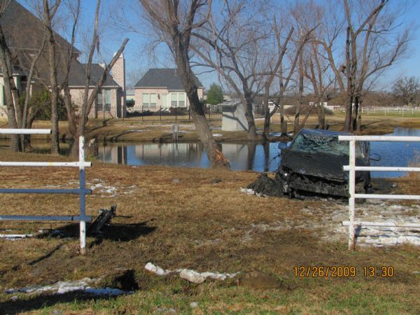 In this Dec. 26, 2009 photo released by Roberts & Roberts law firm, a scene of a deadly crash of the 2008 Toyota Avalon taken by the Southlake Police Department is shown. In the Texas crash, four people died when their 2008 Avalon ripped through a fence, hit a tree and flipped into an icy pond. Toyota has for years blocked access to data stored in devices similar to airline
