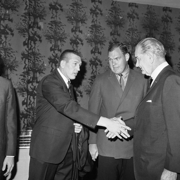 This Feb. 1, 1968, photo shows Baltimore Colts quarterback Johnny Unitas shaking hands with President Johnson as Los Angeles Rams' Merlin Olsen, center, looks on, at the annual Presidential Prayer Breakfast in Washington.  Olsen, a Pro Football Hall of Famer and former television actor from Utah,  died early Thursday, March 11, 2010, at a Los Angeles hospital. He was 69.