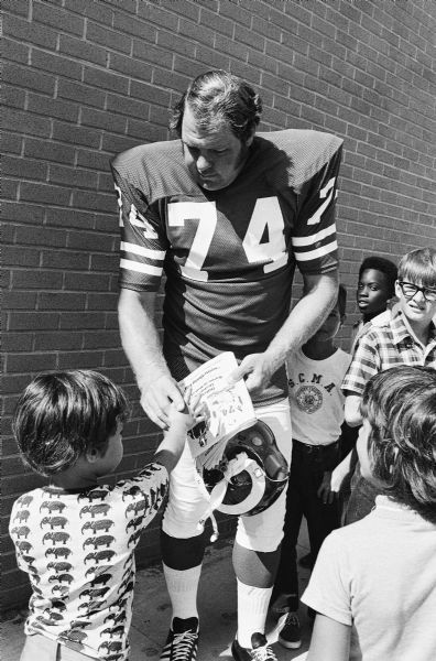 This Nov. 8, 1972 photo shows Los Angeles Rams' defensive tackle Merlin Olsen signing autographs in Los Angeles. Olsen, a Pro Football Hall of Famer and former television actor from Utah,  died early Thursday, March 11, 2010, at a Los Angeles hospital. He was 69.