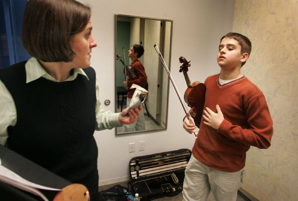 LOS ANGELES,CA-020906- Will's mother, Loree Hagen offers a powerbar to Will as he practices his violin lesson before his class at the Colburn School of Music in Downtown Los Angeles. The powerbar helps Will to maintain his sugar level.  Photo by J.Emilio Flores