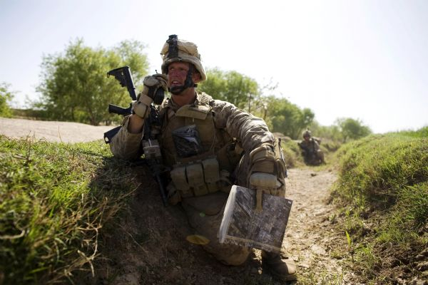 U.S. Marine, Sgt. John Trickler of Townsend, Tennessee,  with the First Battalion, Sixth Marine Regiment, Alpha company, talks on the radio as they are involved in a gunbattle during a patrol in Marjah, Afghanistan, Friday, March 19, 2010. (AP Photo/Dusan Vranic)