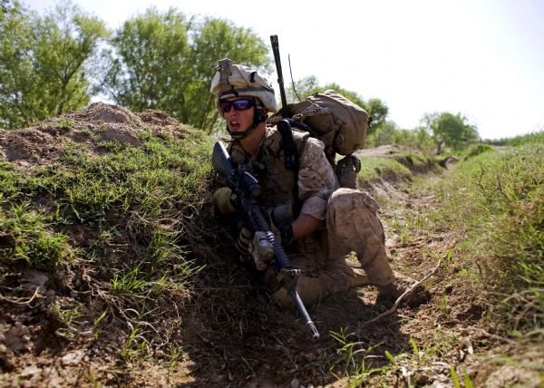 U.S. Marine, Lance Cpl. Brett Whirle of Dunellon, Florida, with the First Battalion, Sixth Marine Regiment, Alpha company, takes cover as they are involved in a gunbattle during a patrol in Marjah, Afghanistan, Friday, March 19, 2010. (AP Photo/Dusan Vranic)
