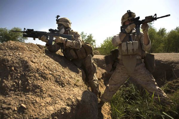 U.S. Marines, Corman Michael Lang, of Camden County, Georgia, right, and Lance Cpl. Ard Bizahaloni of Pinon, Arizona, with the First Battalion, Sixth Marine Regiment, Alpha company, take up positions as they are involved in a gunbattle during a patrol in Marjah, Afghanistan, Friday, March 19, 2010. (AP Photo/Dusan Vranic)