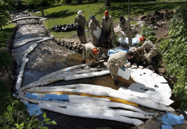 Francisco Kjolseth     The Salt Lake Tribune     Salt Lake City - Crews try and clean up the oil spill flowing down Red Butte creek through Garden Park LDS Ward in Salt Lake on June 14, 2010, after water drained from the small pond pushed more oil through.