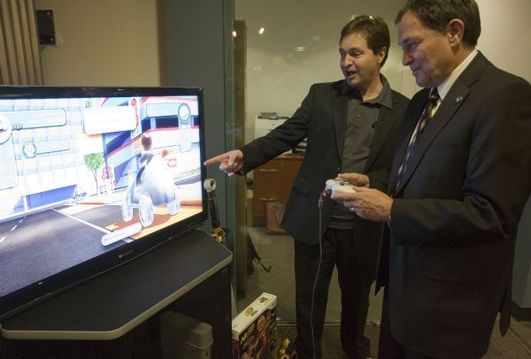 Jim Urquhart  |  The Salt Lake TribuneJon Dean executive producer at Electronic Arts, left, and Utah Governor Gary Herbert play Monopoly Streets Wednesday, July 21, 2010 at Electronic Arts in Salt Lake City. Electronic Arts, one of the major electronic game makers, opened its Salt Lake City office after it moved from Bountiful. 7/21/10