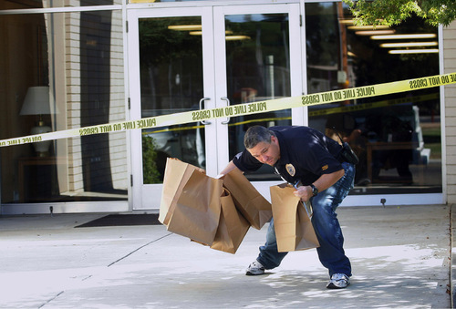 Visalia Police Officer Bob Douglas removes evidence after a shooting that killed lay bishop Clay Sannar of the Church of Jesus Christ of Latter-Day Saints Sunday, Aug. 29, 2010 in Visalia, Calif. (AP Photo/The Fresno Bee, Gary Kazanjian)