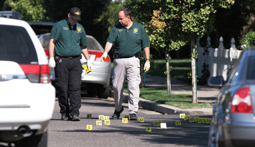 Visalia Police detectives point to an area where a suspect was shot after lay bishop Clay Sannar of the Church of Jesus Christ of Latter-day Saints was shot and killed Sunday, Aug. 29, 2010 in Visalia, Calif. (AP Photo/The Fresno Bee, Gary Kazanjian)