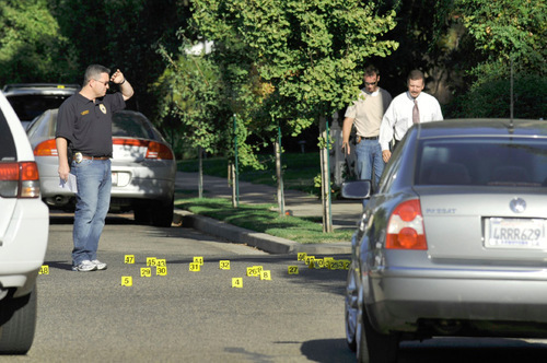 Dozens of evidence markers, many of them marking spent shell casings, dot the street Sunday Aug. 29, 2010 after Visalia police shot and killed a suspect in the fatal shooting at The Chuch of Jesus Christ Latter-Day Saints, in Visalia. (AP Photo/Ron Holman/THE TIMES DELTA)