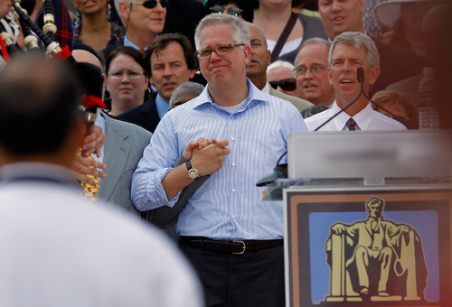 Glenn Beck, center, holds hands with faith leaders at the