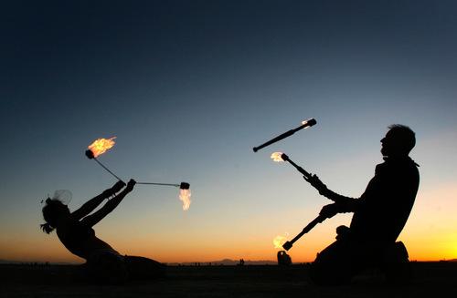 Rick Egan   |  The Salt Lake TribuneSavanah and Chris,  of San Francisco, twirl fire at sunrise, at the Burning Man Festival, Saturday, Sept. 4, 2010.
