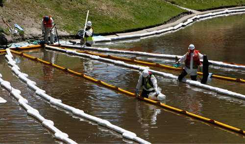 Francisco Kjolseth  |  The Salt Lake Tribune    Salt Lake City - Clean up from the Red Butte creek oil spill continues on Monday, June 28, 2010, as crews wipe down multiple booms set up at the Liberty Park pond.