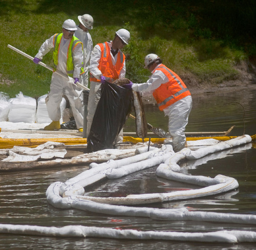Chris Detrick | The Salt Lake TribuneCleanup crews work along the banks of the pond near the east side of Liberty Park Tuesday, June 15, 2010. 33,000-gallons of oil spilled into Red Butte Creek Friday night.