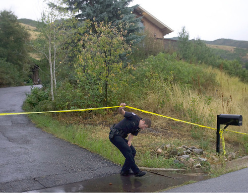Al Hartmann  |  Salt Lake TribuneLayton police officer Mike Corry ducks beneath police tape closing off home at 2184 N. Snowqualme Dr. in the foothills above Layton. Two children, ages 7 and 8, were found dead in the home Wednesday night. Their mother has been arrested in connection with the deaths.